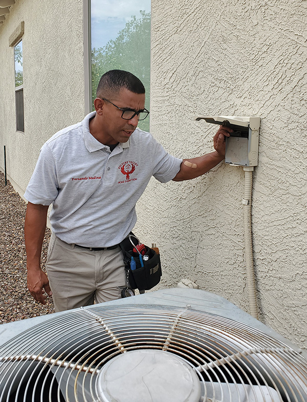 Fernando Medina Inspecting the exterior of a home in Arizona.