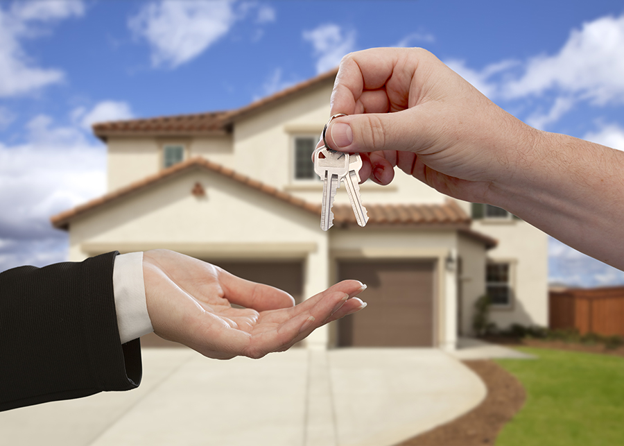 Hands Handing Over the House Keys in Front of a New Home Inspection Services