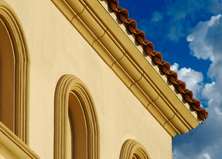 Looking up at a house with stucco walls and tile roof of a house