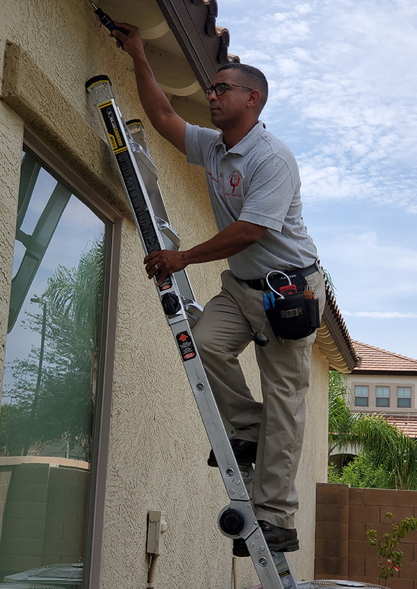 Home Inspector Fernando Medina on a ladder checking the top of a window.